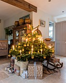 Presents around base of Christmas tree decorated with candles and slices of orange