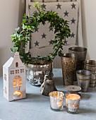 Festive arrangement of ivy wreath, house-shaped lantern and tealight holders