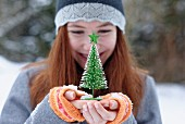 Girl holding little Christmas tree