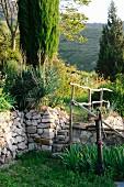 Hand pump in Mediterranean garden with stone wall