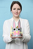 Young woman holding hand-made, paper Easter basket with bunny face