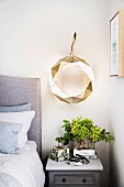Modern aluminum wreath with lighting above the bedside table