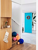 Colorful paper balls on the stairs in the entrance area with blue door