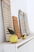 Wooden artworks and fruit on wooden radiator cover with wire-mesh front