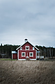 Red, lonely Swedish house under grey cloudy sky