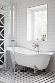 Free-standing clawfoot bathtub below window