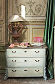 Pink glasses and table lamp on old chest of drawers against panelled wall