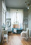 Free-standing bathtub in front of window in historical bathroom