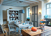 Dining table in grey and white country-house kitchen