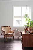 Vintage Sessel und Dreirad-Pferd vor Fenster, im Vordergrund Sideboard mit Zimmerpflanze