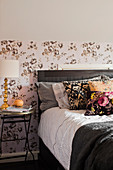 Scatter cushions on double bed and table lamp on bedside table against patterned wallpaper