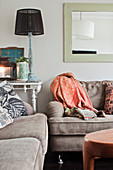 Scatter cushions and blanket on sofa set with table lamp on console table in background