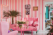 Striped wallpaper in kitsch living room decorated entirely in pink and hot pink