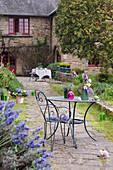 Metal garden furniture in garden of French farmhouse