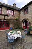 Set garden table in courtyard of French farmhouse