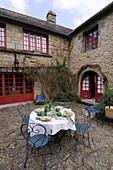 Set garden table in courtyard of French farmhouse