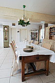White tablecloth on long wooden table with wicker chairs