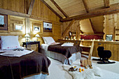 Twin beds and cubby bed, furs and toys on floor in wood-clad chalet