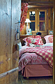 View into rustic bedroom with textiles in shades of red and pink