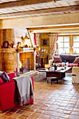 Offener Wohnraum mit rotem Sessel, Kamin mit Holzverkleidung, Polstergarnitur und Couchtisch im Chalet