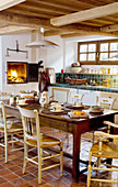 Wooden table and chair in kitchen with wood-fired oven