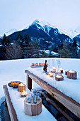Romantically set wooden table and bench in snowy landscape