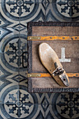 Old chest with a cobbler on patterned cement tiles