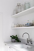 Two shelves with glasses over the marble-topped sink