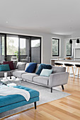 Eleganter, offener Wohnraum mit grauen und blauen Polstermöbeln, im Hintergrund Theke mit Barhockern