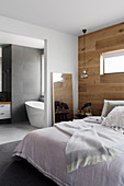 Double bed in bedroom with wall made from recycled oak, view of bathroom ensuite