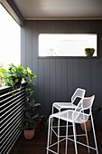 White metal bar stool on balcony with plants