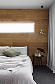 Double bed in the bedroom with wall made of recycled oak
