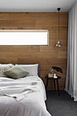 Doppelbett im Schlafzimmer mit Wand aus recyceltem Eichenholz