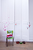 White fitted wardrobe with butterfly motifs, clothes on chair and children's shoes in room in period building