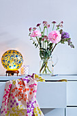 Flowers in glass jug and retro table lamp on chest of drawers