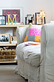 Scatter cushions on loose-covered sofa in front of shelves