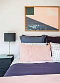Double bed with pillows, bedside table with lamp and modern picture in the bedroom