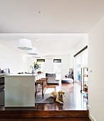 Kitchen island with bar stools in open split-level living area, dog on parquet floor