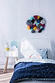 Children's room with dot pattern and wall decoration made of colorful pompoms