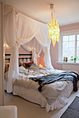 Romantic canopy above bed with crumples bed linen