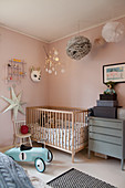 Cot in nursery with pink walls