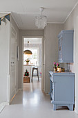 Blue kitchen cupboard in white Scandinavian-style hallway