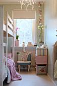 Bunk-beds in narrow children's bedroom in pastel shades