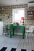 Green table and retro wallpaper in kitchen