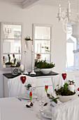 Weihnachtlich gedeckter Tisch im ländlichen Esszimmer in Weiß