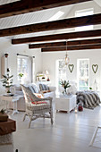 White living room decorated for Christmas with exposed roof structure
