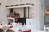 View across dining table to festively decorated wood-fired kitchen cooker