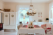 Festively set table in white country-house-style dining room
