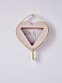 Homemade jewelry holder in the shape of a heart on the wall