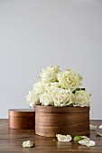 Bunch of white roses on top of dark chip-wood box